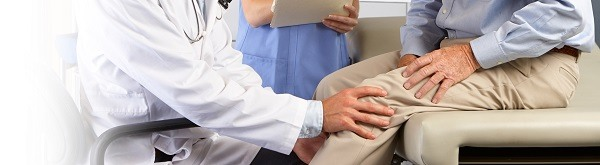 Male doctor examining male patient with knee pain.